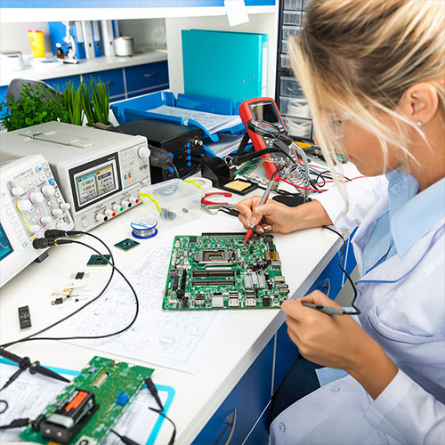 Young woman working on a circuit board to depict our products and services clients